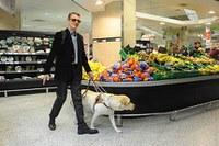 persona ciega con perro guía en el supermercado