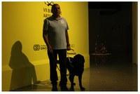 Perro guía junto a su instructor en la bienal de arte