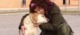 Una adoptante abraza a su perro guía jubilado