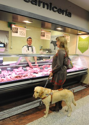 Una usuaria con su perro guía comprando en una carnicería