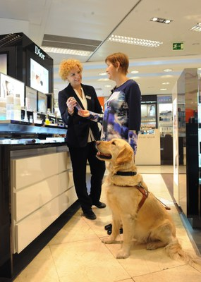 Una usuaria con su perro guía es atendida en un centro comercial