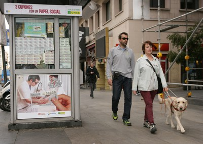 Un instructor supervisa a su alumna durante un paseo junto a un kiosko de la ONCE