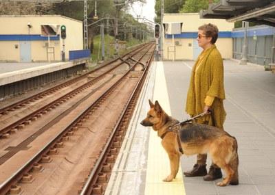 Una usuaria con su perro guía esperando el metro en el andén