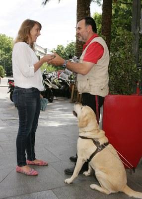 un vendedor de la ONCE con su perro guía atiende a una compradora